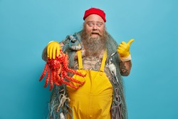 Excited bearded seaman points away on blank space wears yellow gloves and overalls holds big red octopus has tattooed body isolated over blue background. Navy life concept. Seafarer at sailboat