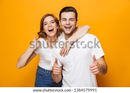 Excited beautiful couple wearing white t-shirts standing isolated over yellow background, showing thumbs up #1384579991