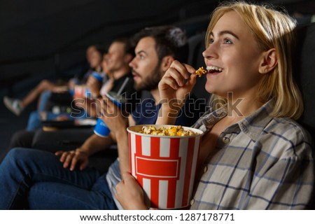 Excited beautiful female watching new entertaining comedy in cinema hall. Cheerful young blonde laughing, eating popcorn and enjoying free time on weekend. Concept of happiness and fun.