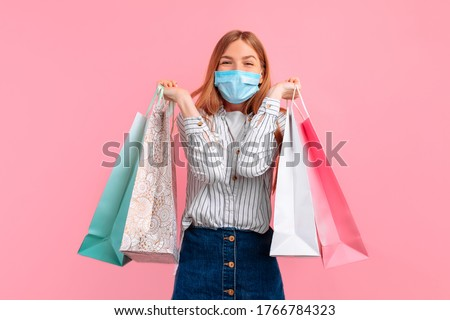 excited beautiful girl in a medical protective mask on her face, holding shopping bags isolated on a pink background. Shopping, quarantine, coronavirus