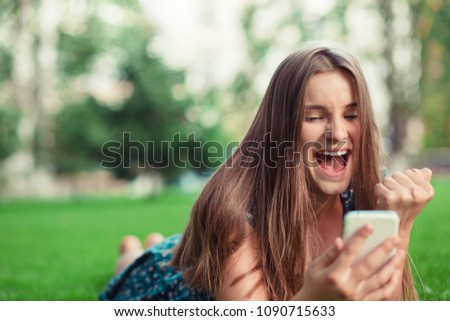 Excited beautiful girl receiving a sms message with good news in a mobile phone outside in park lying down on green lawn trees on background. Multicultural model, mixed race asian russian teenage girl