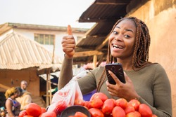 excited beautiful young african woman in a local african market using her smartphone giving thumbs up