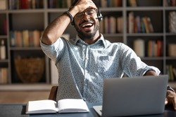 Excited biracial male call center agent in headset have fun laugh working on computer online, overjoyed African American man busy studying or watching funny training webinar on computer gadget
