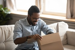 Excited biracial young man sit on couch at home unpack cardboard box with Internet order, happy African American male open carton package at home, shopping on web, good delivery service concept
