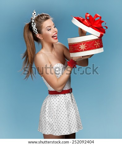 Excited birthday girl opening surprise gift / set photos of beautiful young retro pinup woman on blue background