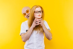 Excited bizarre strange odd couple have fun with plastic mannequin.  Weird relationship. Happy adult bald man in orange glasses isolated on yellow background. Oddball rebel with hairy girl head