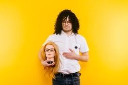 Excited bizarre strange odd foolish guy have fun with plastic mannequin.  Weird relationship. Happy adult man in black curly wig isolated on yellow background. Oddball rebel with hairy girl head