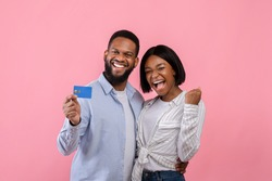 Excited black couple with credit card making YES gesture, promoting contactless shopping over pink studio background. Affectionate young lovers buying gifts for Valentine's Day online, using bank card