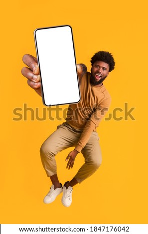 Excited black guy holding smartphone, showing blank screen, jumping up over orange studio background. Handsome african american young man recommending new mobile application, collage Foto stock ©