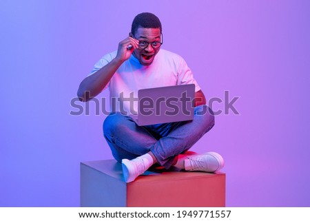 Excited Black Male In Eyeglasses Sitting On Big Cube With Laptop, Looking At Screen With Amazement, African American Student Guy Posing In Neon Light Over Purple Studio Background, Free Space Foto stock ©