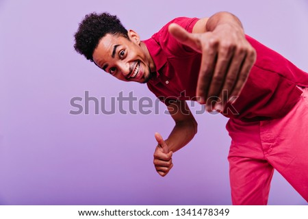 Excited black male model dancing in studio. Funny emotional man in red t-shirt looking to camera with smile.