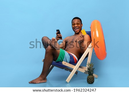 Excited black man holding credit card and smartphone, shopping online in lounge chair on blue studio background. Cool African American guy buying goods in web store during summer vacation Foto stock ©