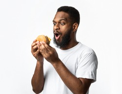 Excited Black Man Holding Unhealthy Burger Posing Standing On White Studio Background. Junk Food Eater Looking At Tasty Unhealthy Hamburger With Opened Mouth. Nutrition And Overeating Habit