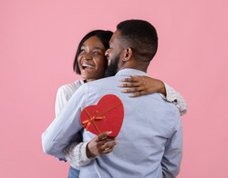 Excited black woman holding heart shaped gift box and hugging her boyfriend on pink studio background. Lovely African American couple celebrating Valentine's Day together