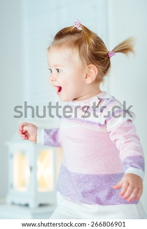 Excited blond little girl with ponytail jumping on bed, laughing and screaming. White interior, bedroom, night lamp