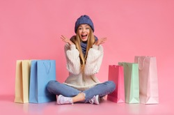 Excited blonde girl in winter blue set sitting on floor among colorful shopping bags over pink background, raising hands in emotional gesture, copy space