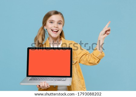 Excited blonde little kid girl 12-13 years old in yellow jacket isolated on blue background. Childhood lifestyle concept. Hold laptop pc computer with blank empty screen point index finger aside up Stock photo ©