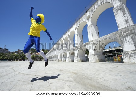 Excited blue Brazilian football player spectator celebrating in team colors at Lapa Arches in Rio de Janeiro