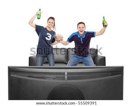 Excited boy and girl watching sport on a TV isolated on white background