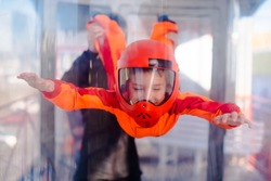 Excited boy in orange helmet flying in aerodynamic tube (wind tunnel). Skydiving training.