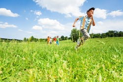 Excited boy runs away from his mates in field during summer time