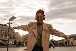 Excited brunette woman in beige trench coat listens to music in red headphones and dances in great mood outdoors during sunset.