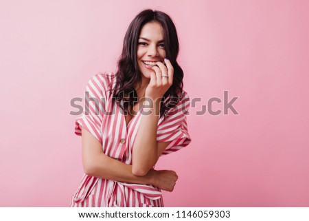 Excited brunette woman wears ring smiling on pink background. Indoor photo of gorgeous dark-haired girl in elegant striped dress. #1146059303
