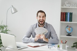 Excited business man in gray shirt sit at desk work on laptop pc computer in light office on white wall background. Achievement business career concept. Hold fan of cash money in dollar banknotes