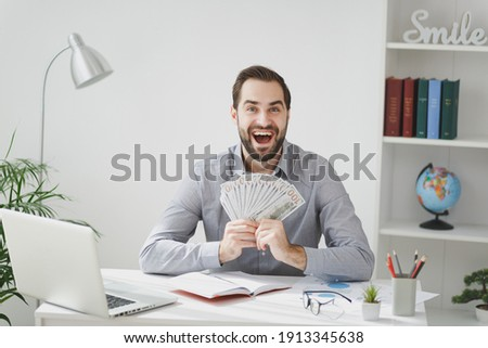 Excited business man in gray shirt sit at desk work on laptop pc computer in light office on white wall background. Achievement business career concept. Hold fan of cash money in dollar banknotes Сток-фото ©
