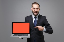 Excited business man in suit shirt tie posing isolated on grey background. Achievement career wealth business concept. Mock up copy space. Point finger on laptop pc computer with blank empty screen