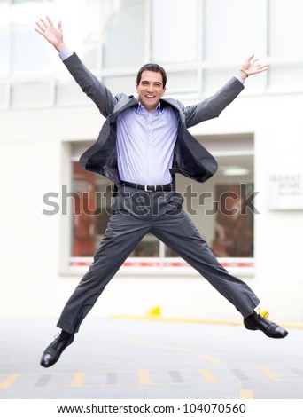 Excited business man jumping and looking very happy