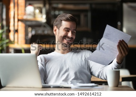 Excited business man student reading postal mail letter overjoyed by great news, happy male winner holding paper bill with loan approval celebrate taxes refund receive salary rise payment sit at desk