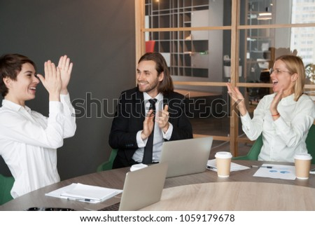 Excited business team applauding congratulating partner with personal success or professional achievement at meeting, happy colleagues clapping hands motivated by corporate victory, good work results