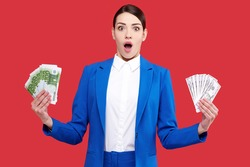 Excited business woman with money, female holding euro and dollar banknotes, young girl in blue suit in red isolated background