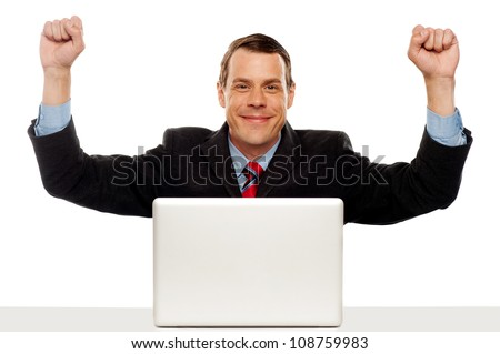 Excited businessman celebrating success with his arms raised up. Sitting in font of laptop