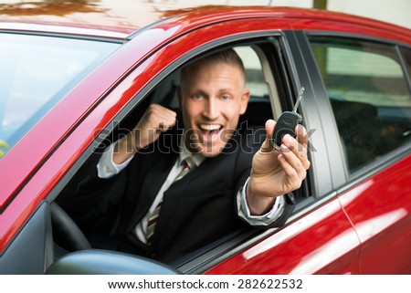Excited Businessman Sitting In A Car Showing New Car Key