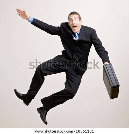 Excited businessman with briefcase jumping in mid-air cheering and celebrating his success