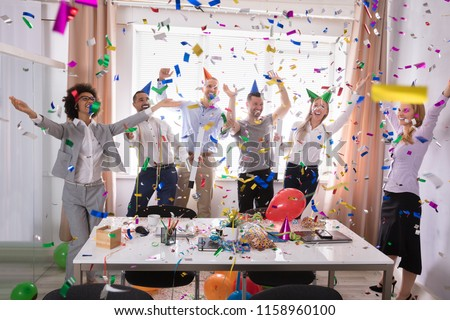 Excited Businesspeople Having Fun Raising Their Arms Among Party Confetti #1158960100