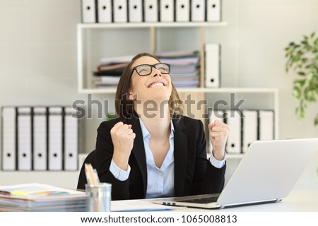 Excited businesswoman celebrating success looking above at office #1065008813