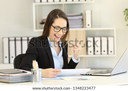 Excited businesswoman checking gorwth graph celebrating success at office #1348223477