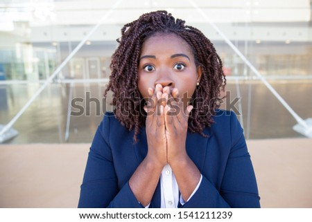 Excited businesswoman shocked with surprising news. Young African American business woman with wide eyes standing outside, covering mouth with hands. Surprise concept