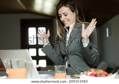 Excited businesswoman working at PC during breakfast #209351983