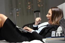 Excited bussinesswoman during a business travel finding online content in a laptop lying on a bed at hotel room