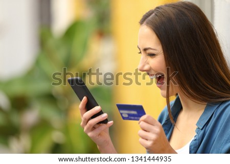 Excited buyer buys on line with credit card and smart phone in a colorful street