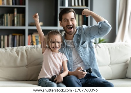 Excited by videogame victory little kid girl and her father raised hands scream with joy sit on sofa at home. Father his small daughter holds playing celebrate success feels happy