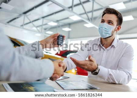 Excited car buyer with face mask shaking hands with car seller and taking car keys while sitting in car salon.