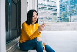 Excited casual Asian female in yellow hoodie and blue jeans surfing mobile with great surprise while sitting on street steps