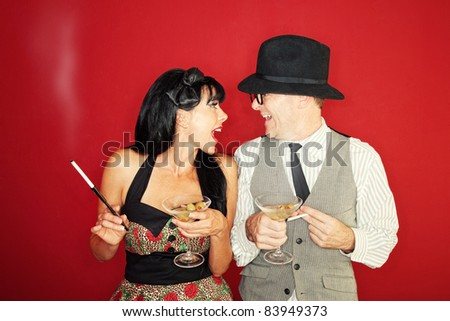 Excited Caucasian couple enjoy martini and cigarette over maroon background