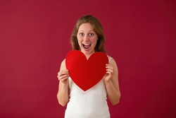 Excited Caucasian female with sparkling heart on valentines day. Happy woman holding love symbol on red background. Blonde girl full of happiness.