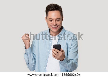 Excited Caucasian millennial man isolated on grey studio background look at smartphone happy get good text message, smiling male client use cellular read great news, win lottery on mobile app online